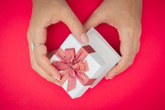 Hand holding white gift box, Used for New Year`s Eve, Christmas, Birthday, Valentine`s Day. on redbackground royalty free stock photos