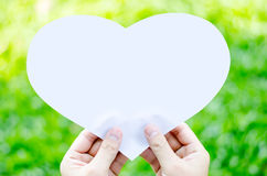 Hand holding white heart paper on blur grass background Royalty Free Stock Photography