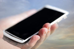 Hand holding white mobile phone Royalty Free Stock Images