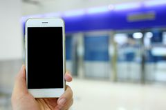 Hand holding white mockup smartphone with subway  station backgr Royalty Free Stock Photography
