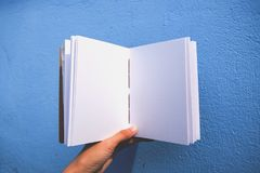 Hand holding a white paper book royalty free stock image
