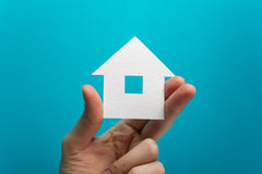 Hand holding white paper house figure on blue background. Real Estate Concept. Ecological building. Copy space top view. Stock Photography