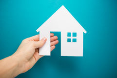 Hand holding white paper house figure on blue background. Real Estate Concept. Ecological building. Copy space top view. Royalty Free Stock Photos