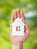Hand holding white paper house figure on green background stock photos