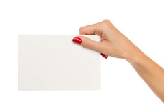 Hand Holding White Paper Sheet. Close up of woman's hand with red nails holding blank white paper sheet. Studio shot isolated on white Stock Image
