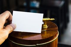 Hand holding white paper on wooden piggy bank with empty and copy space for text input.  Stock Image