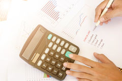 Hand holding white pen on check list. With calculator on white paper graph on wooden table for choice Royalty Free Stock Image