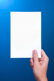 Hand holding white sheet paper card on blue. Close-up hand holding white sheet paper card on blue Royalty Free Stock Photos