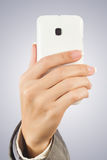 Hand holding white smart phone Stock Image