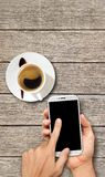 Hand holding White Smart phone on wood coffee table Royalty Free Stock Images