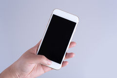 Hand holding white smartphone with black screen Royalty Free Stock Photography
