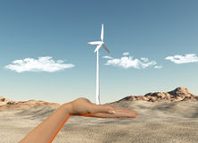 Hand holding wind turbine against a desert Stock Photos