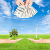 Hand holding wind turbine with tree and US Dollars banknote Stock Photography