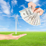 Hand holding wind turbine and US Dollars banknote Stock Photos