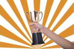 Hand holding winner trophy cup. In a championship stock photography