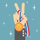 Hand holding a winners medal. And showing victory fingers sign Stock Photo
