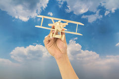 Hand holding wooden airplane model Royalty Free Stock Images
