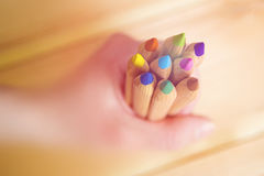 Hand holding wooden colorful pencils against wooden background.  Stock Photo
