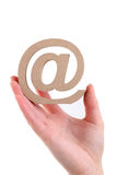 Hand holding wooden email symbol Stock Photo