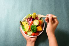 Hand holding wooden fork and eating salad. Hand holding wooden fork and eating mixed vegetables salad, healthy food Royalty Free Stock Image