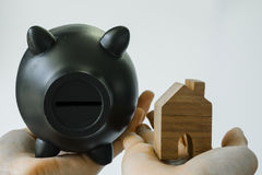 hand holding wooden miniature house and black piggy bank as financial saving or mortgage house loan concept royalty free stock photography