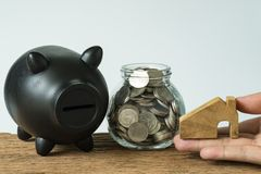 Hand holding wooden miniature house with coins in jar and black. Piggy bank as financial saving or mortgage house loan concept stock photo