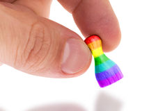 Hand holding wooden pawn, rainbow flag Stock Photo
