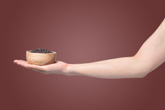 Hand holding  wooden plate with black rice grain  on isolated gradient red background. Royalty Free Stock Images
