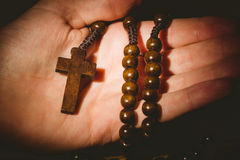 Hand holding wooden rosary beads Stock Photo