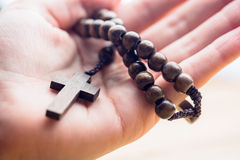 Hand holding wooden rosary beads Royalty Free Stock Photos