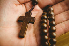 Hand holding wooden rosary beads Stock Image