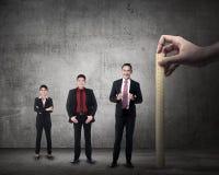 Hand holding wooden ruler, mesuring employee performance Stock Photos