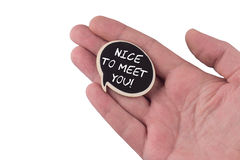 Hand holding a wooden speech bubble with nice to meet you text o Stock Image