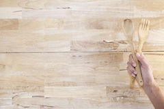 Hand holding a wooden spoon on wood background. Stock Photos
