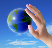 Hand holding world. World and women hand holding on blue sky royalty free stock photos