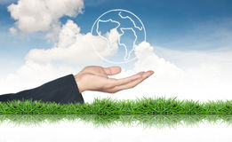 Hand holding world map icon. Against cloud blue sky Stock Photo