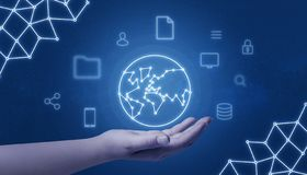 Hand holding world network concept map surrounded with internet of things icons on blue background.  stock images