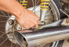 Hand holding wrench with motorcycle repair Stock Photos