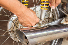 Hand holding wrench with motorcycle repair Royalty Free Stock Photography