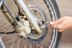 Hand holding wrench with motorcycle repair Stock Images