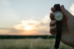 Hand holding wristwatch at sunset