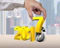 Hand holding 2017 year. Golden number, with city buildings background Stock Images