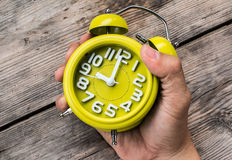 Hand Holding Yellow Alarm Clock Stock Images