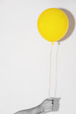 Hand holding yellow balloon on white wall Royalty Free Stock Photo