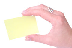 Hand holding a yellow blank notecard. Woman Hand Holding Yellow Post-It Stock Photography