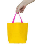 Hand holding yellow fabric bag stock photos