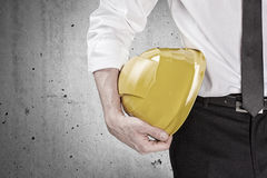 Hand holding a yellow hard hat Royalty Free Stock Image