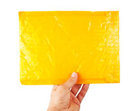 Hand holding yellow mail package. Isolated on white Royalty Free Stock Photography