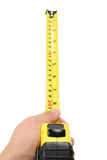 Hand holding yellow measuring tape Stock Photography