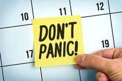 Hand Holding Yellow Paper Note With Words Don`t Panic. On Calendar Royalty Free Stock Image